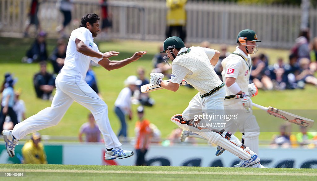 Sri Lankan bowler Chanaka Welegedara (L) takes evasive action as Australian batsmen Ed Cowan (C) and David Warner (R) take more runs on the fourth day of the first cricket Test match, in Hobart on December 17, 2012. AFP PHOTO/William WEST IMAGE RESTRICTED TO EDITORIAL USE - STRICTLY NO COMMERCIAL USE