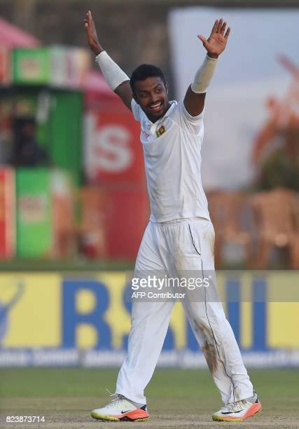 Sri Lankan bowler Danushka Gunathilaka celebrates after dismissing Indian batsman Abhinav Mukund during the third day of the first Test match between...