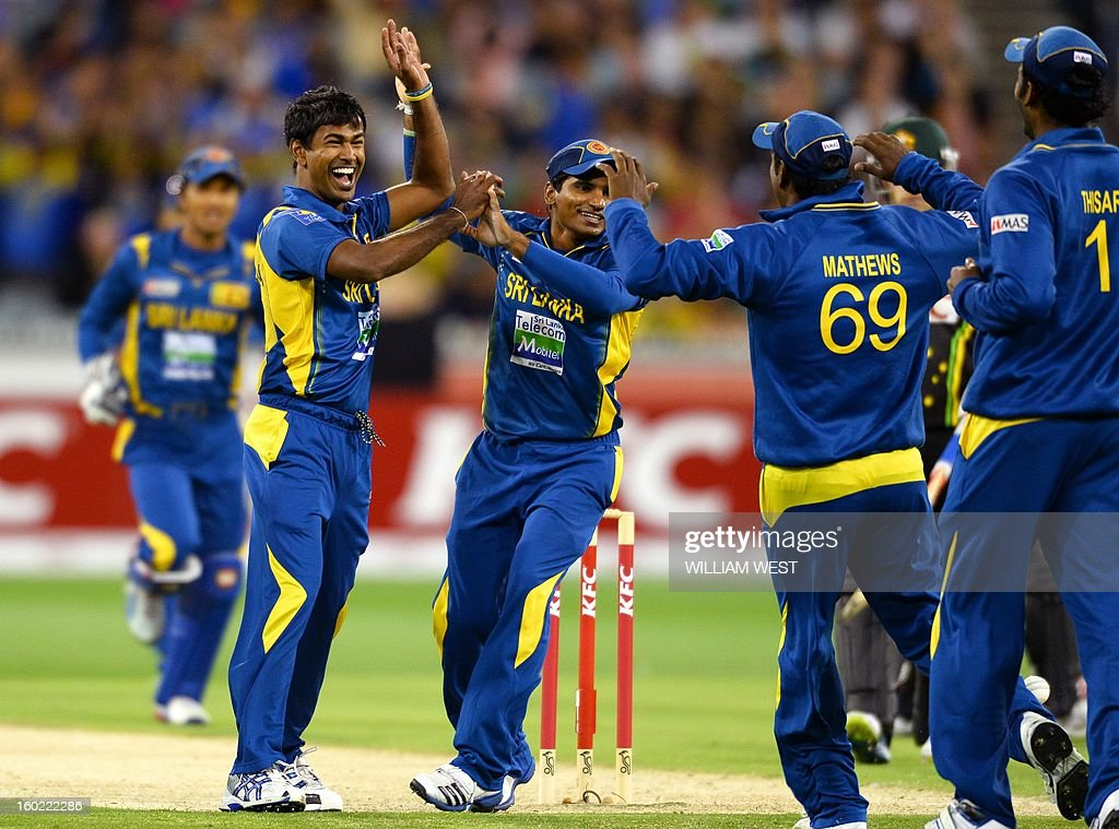Sri Lankan bowler Nuwan Kulasekara (2/L) is congratulated by teammates after dismissing Australian batsman David Warner during their Twenty20 match played at the Melbourne Cricket Ground (MCG), on January 28, 2013. William WEST IMAGE