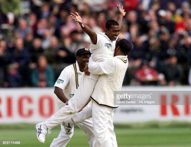 Sri Lankan bowler Ruchira Perera is embraced by teammate Hashan Tillakaratne with captain Sanath Jayasuriya running in to celebrate after trapping...