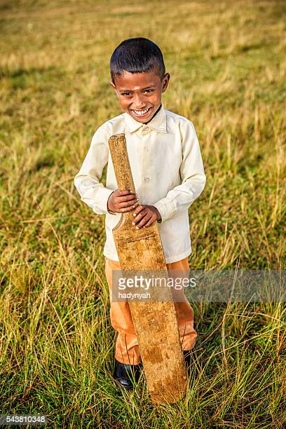 Sri Lankan boy posing with cricket bat on tea plantation