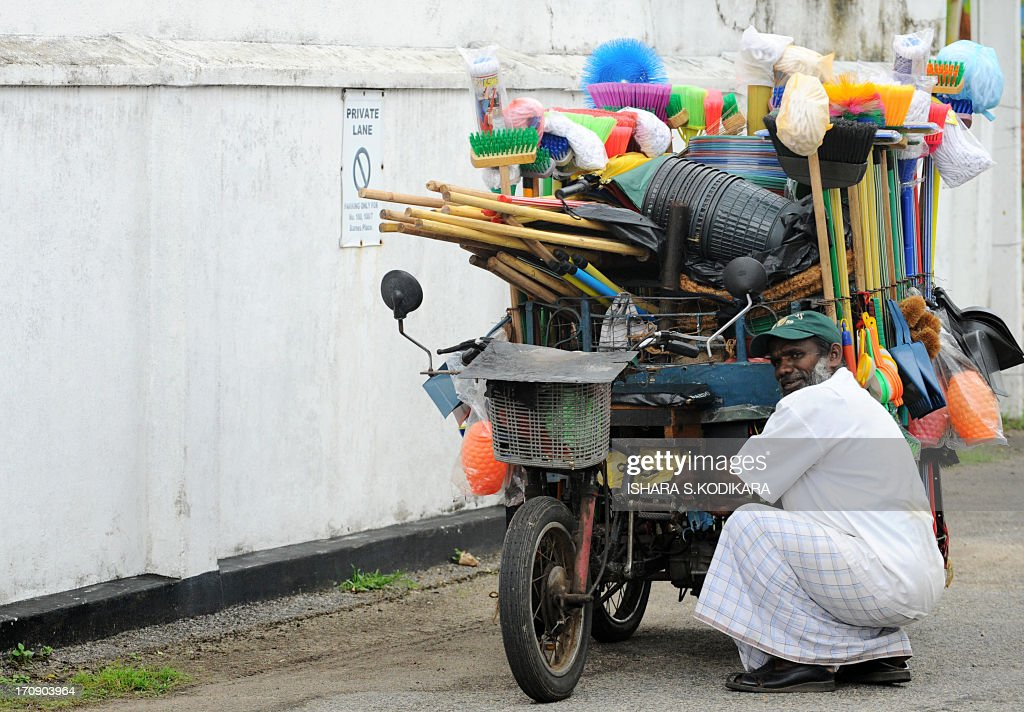 Sri Lankan brush vendor Mohamed Suwais (57) repairs his make-shift electric-powered tricycle at the Cinnamon Gardens diplomatic quarter in Colombo on June 20, 2013. Suwais sells his wares in the upmarket neighbourhood competing with supermarkets and departmental stores in a country emerging as a middle-income countruy after ending 37 years of ethnic bloodshed in 2009. AFP PHOTO/Ishara S