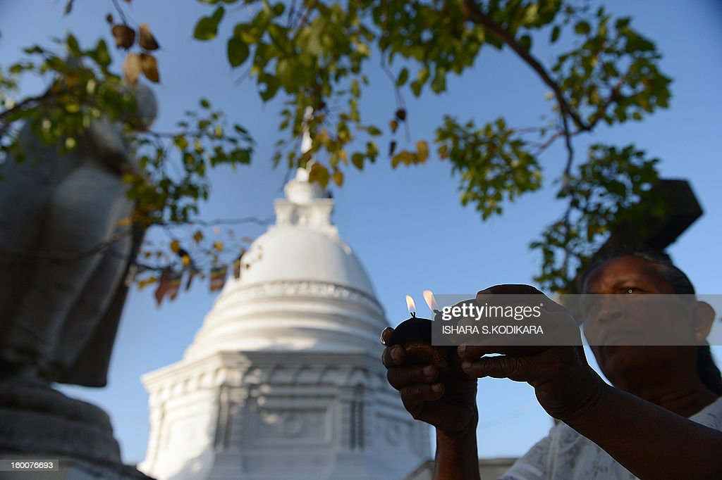 A Sri Lankan Buddhist devotee holds lit oil lamps during Poya, a full moon religious festival at the Gangaramaya Temple in Colombo on January 26, 2013. The predominantly Buddhist Island nation marks every full moon as a key religious holiday. AFP PHOTO/ Ishara S. KODIKARA