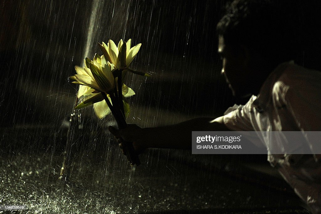 A Sri Lankan Buddhist holds out flowers under a fountain before praying at the Kelaniya Temple on December 31, 2012, in Kelaniya. Many Sri Lankans marked the beginning of the 2013 New Year with religious ceremonies. AFP PHOTO/Ishara S. KODIKARA