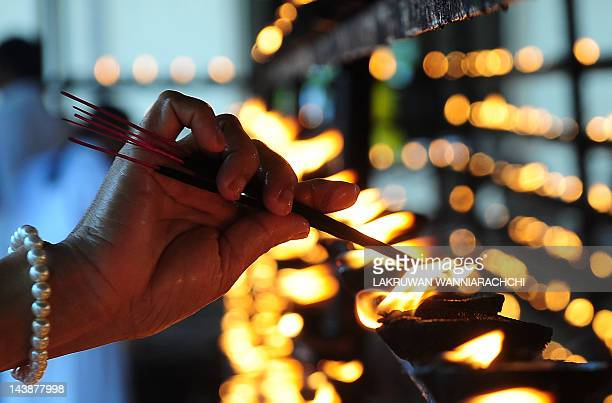 A Sri Lankan Buddhist lights an oil lamp during Vesak at the Temple in Colombo on May 5 2012 Vesak day which is a major holiday in the...