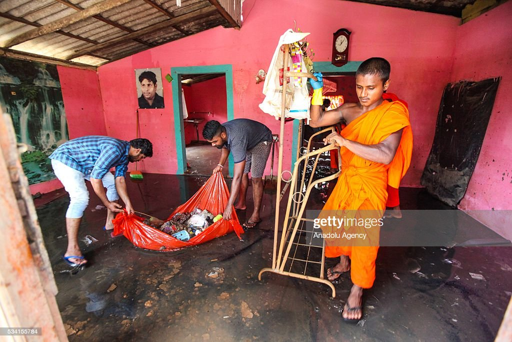 A Sri Lankan Buddhist monk helps to clean damaged house as the water level starts to decline in Wellampitiya, neighborhood of Colombo, Sri Lanka on May 25, 2016.