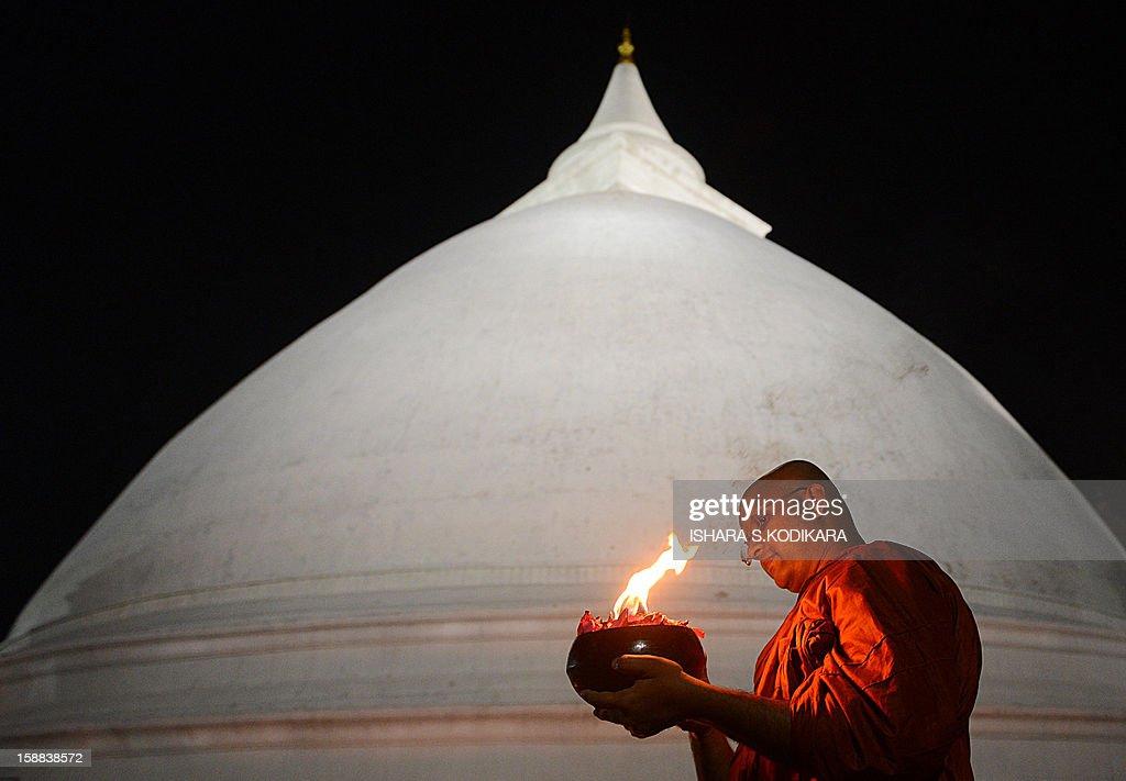 A Sri lankan buddhist monk offers special prayers at the Kelaniya Temple on December 31, 2012, in Kelaniya. Many Sri Lankans marked the beginning of the 2013 New Year with religious ceremonies. AFP PHOTO/Ishara S. KODIKARA