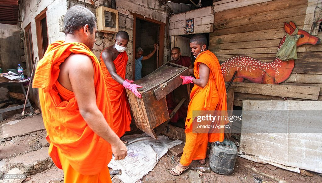 Sri Lankan Buddhist monks help to clean damaged house as the water level starts to decline in Wellampitiya, neighborhood of Colombo, Sri Lanka on May 25, 2016.
