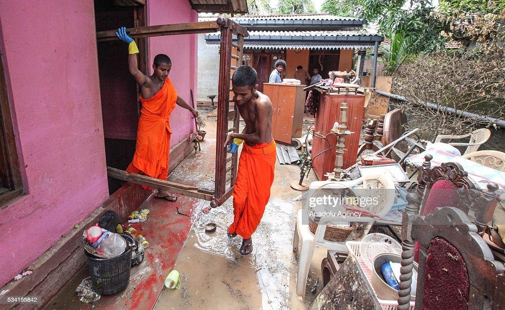 Sri Lankan Buddhist monks help to clean damaged house as the water level starts to decline in Wellampitiya, neighborhood of Colombo, Sri Lanka on May 25, 2016.