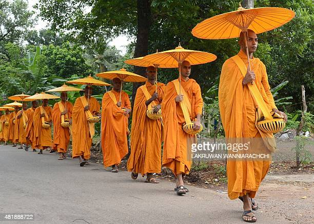 Sri Lankan Buddhist monks walk in line as they seek offerings of food in Colombo on July 25 2015 The Buddhist majority nation later in the month will...