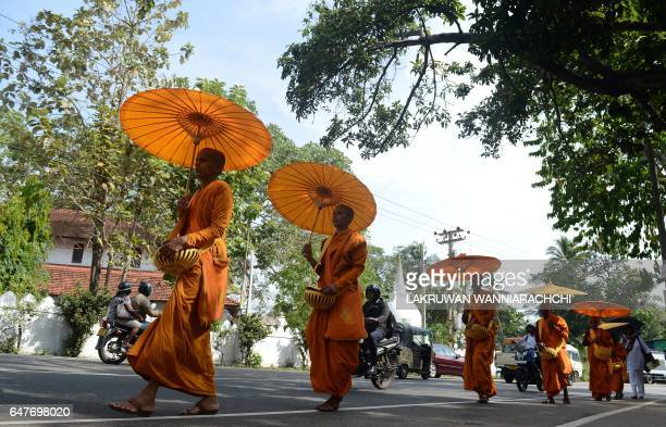 Sri Lankan Buddhist monks walk in line as they seek offerings of food in Colombo on March 4 2017 The Buddhist majority nation later in the month will...