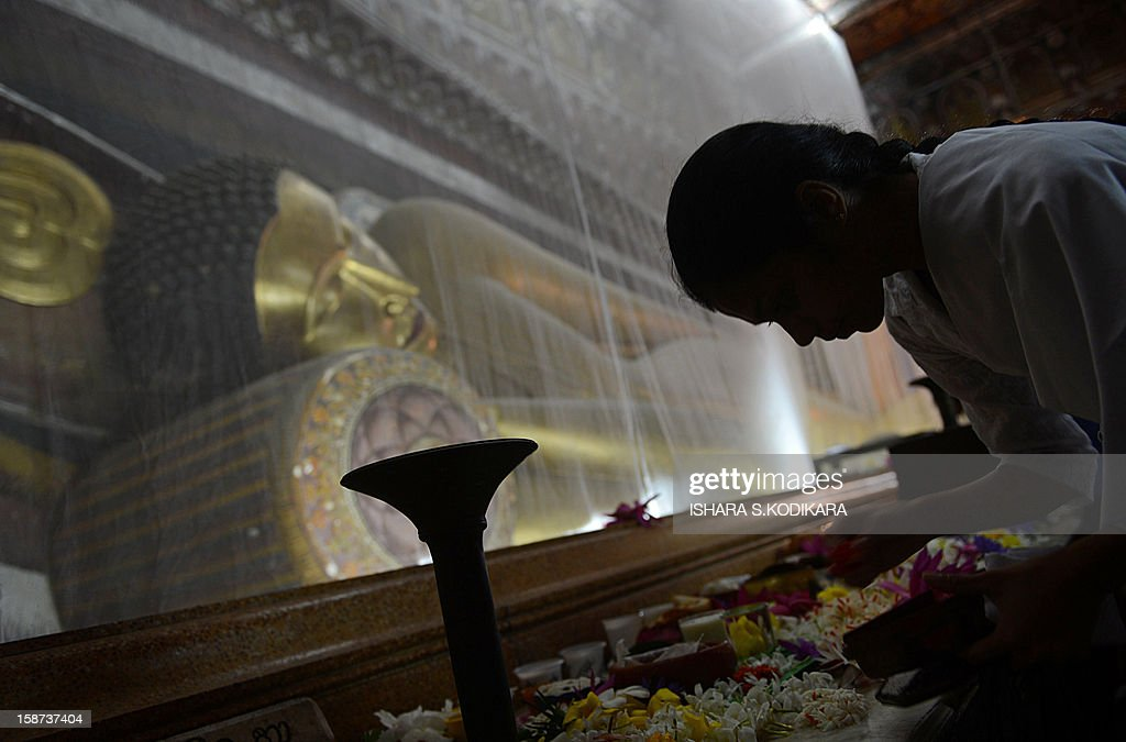 A Sri Lankan Buddhist offers prayers during Poya, a full moon religious festival, at the Kelaniya Temple in Kelaniya on December 27, 2012. The predominantly Buddhist Island nation marks every full moon as a key religious holiday. AFP PHOTO/ Ishara S. KODIKARA