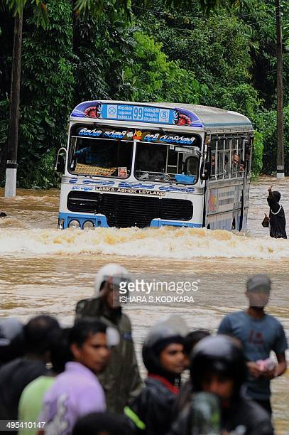 Sri Lankan bus commuters travel through a flooded stretch of road after heavy monsoon rains caused havoc in the western southern and central regions...