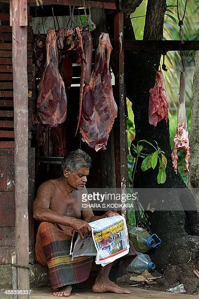 A Sri Lankan butcher reads a newspaper as he waits for customers at a market in Wattala on May 6 2014 Sri Lanka's economy recorded 80 percentplus...