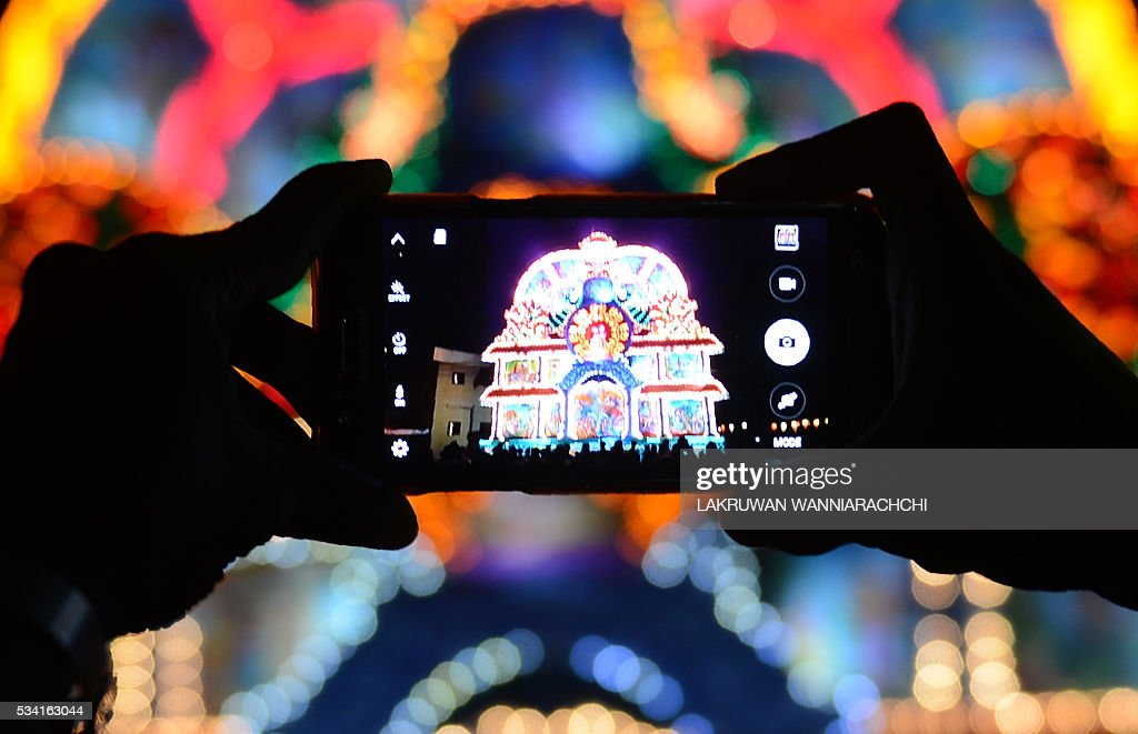 Sri Lankan bysatnders take a photograph of a giant display featuring a seated Buddha during the annual Vesak Buddhist festival celebrations in Colombo on May 25, 2016. Sri Lankan Buddhists are celebrating Vesak, which commemorates the birth of Buddha, his attaining enlightenment and his passing away on the full moon day of May, which falls on May 21 this year. / AFP / LAKRUWAN