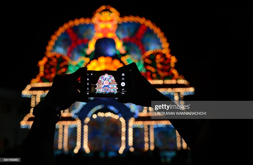 Sri Lankan bystanders take a photograph of a giant display featuring a seated Buddha during the annual Vesak Buddhist festival celebrations in...