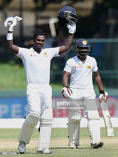 Sri Lankan captain Angelo Mathews celebrates after scoring a century as teammate Kusal Perera looks on during the fifth and final day of the third...
