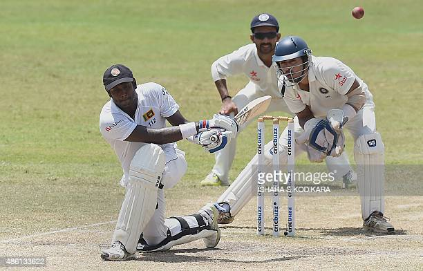 Sri Lankan captain Angelo Mathews plays a shot as Indian wicketkeeper Naman Ojha looks on during the fifth and final day of the third and final Test...