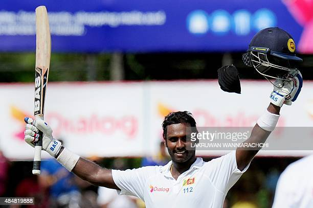 Sri Lankan captain Angelo Mathews raises his bat and helmet in celebration after scoring a century during the third day of the second Test match...