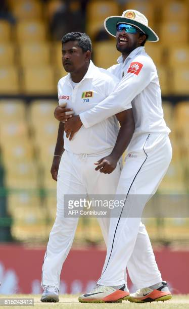 Sri Lankan captain Dinesh Chandimal and Rangana Herath celebrate after he dismissed Zimbabwe's cricketer Hamilton Masakadza during the Third day of...