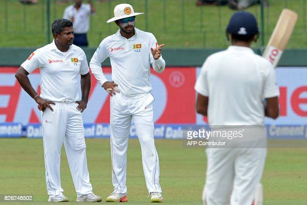 Sri Lankan captain Dinesh Chandimal speaks with teammate Rangana Herath during the second day of the second cricket Test match between Sri Lanka and...
