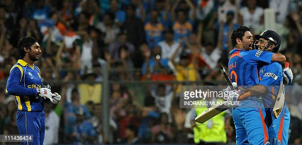 Sri Lankan captain Kumar Sangkkara looks on as Indian captain Mahendra Singh Dhoni and teammate Yuvraj Singh celebrate after victory in the Cricket...