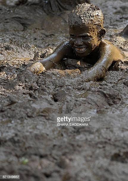 A Sri Lankan child takes part in a traditional game in a muddy field during Sinhala and Tamil New Year celebrations in Kirindiwela on April 15 2016...