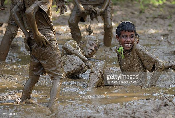 Sri Lankan children take part in a traditional game in a muddy field during Sinhala and Tamil New Year celebrations in Kirindiwela on April 15 2016...