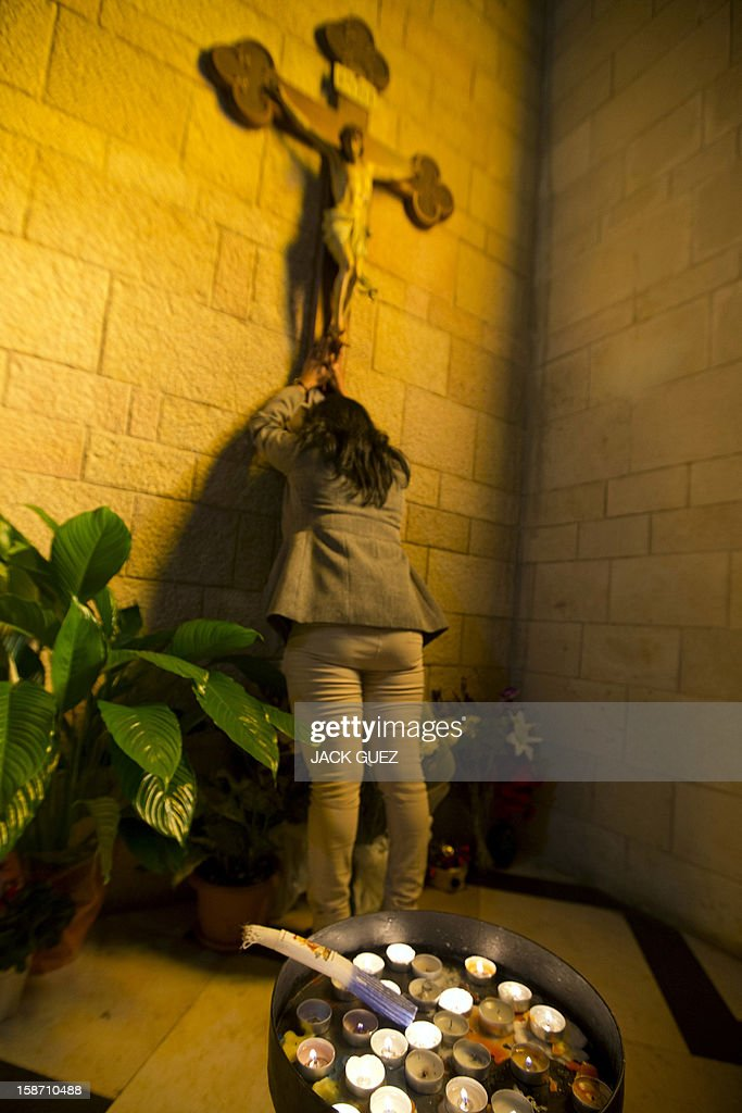A Sri Lankan Christian pilgrim prays in the Nazareth's Basilica of the Annunciation built on the site where Christians believe Virgin Mary was told by the angel Gabriel that she would give birth to Jesus Christ, in the northern Arab-Israeli city of Nazareth on December 25, 2012.