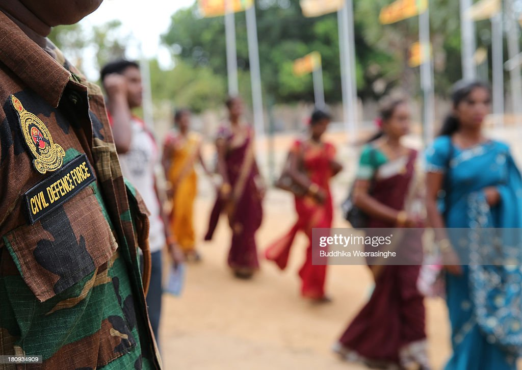 A Sri Lankan Civil Defence Force officer stands guards as women walk to a wedding ceremony at the Civil Defence Force military camp on September 18, 2013 in Vishwamadu, Sri Lanka. A former female Tamil rebel and a Sinhalese military officer were legally married today in Sri Lanka's war-torn Northern province. Sri Lanka suffered through a 26-year civil war between the Tamil Tigers and the Sri Lankan military which ended in 2009. On September 21 Sri Lankans of the Northern Province will head to the polls for provincial council elections for the first time since the conflict began.