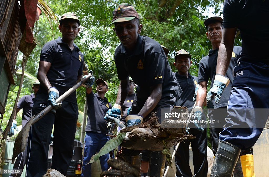 Sri Lankan Civil Security Department personnel clean up flood damage in the Colombo suburb of Kaduwela on May 26, 2016. Floods subsided across Sri Lanka revealing the full extent of damage from last week's heavy rains that also triggered landslides, officials said as the death toll crossed 100. / AFP / LAKRUWAN