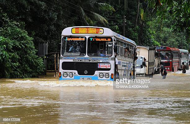 Sri Lankan commuters travel through a flooded road in Puwakpitiya on June 3 2014 after heavy monsoon rans caused havoc in the western southern and...