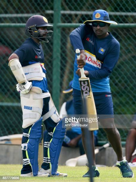 Sri Lankan cricket batting coach Avishka Gunawardene instructs player Niroshan Dickwella during a practice session at the Pallekele International...