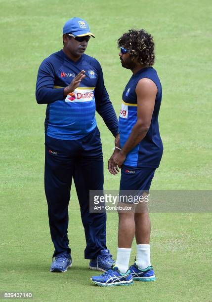 Sri Lankan cricket bowling coach Chaminda Vaas chats with Lasith Malinga during a practice session at the Pallekele International Cricket Stadium in...