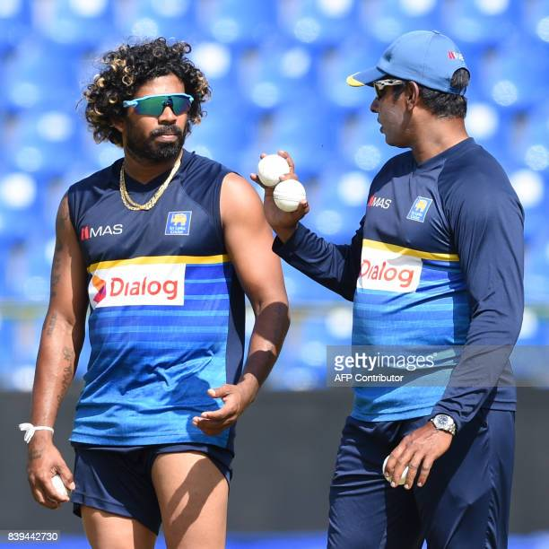Sri Lankan cricket bowling coach Chaminda Vaas chats with Lasith Malinga at a practice session at the Pallekele International Cricket Stadium in...