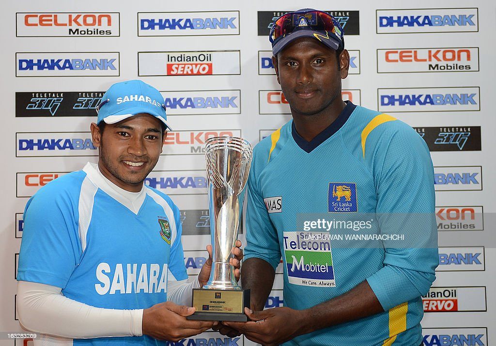 Sri Lankan cricket captain Angelo Mathews (R) and Bangladesh cricket captain Mushfiqur Rahim (L) pose for photographers with the trophy during a press conference in Galle on March 7, 2013. Sri Lanka will play two Tests, three one-dayers and one Twenty20 cricket matches against Bangladesh, with the first Test to start March 8 in Galle.
