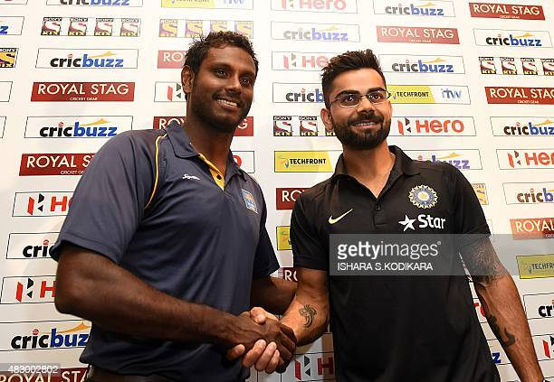 Sri Lankan cricket captain Angelo Mathews and Indian cricket captain Virat Kohli shake hands as they pose at a press conference in Colombo on August...