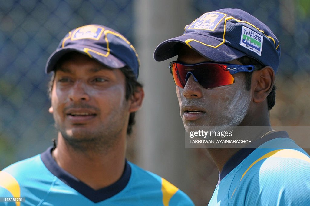 Sri Lankan cricket captain Angelo Mathews (R) and Kumar Sangakkara (L) watch other players during a practice session at the Galle International Cricket Stadium in Galle on March 7, 2013. Sri Lanka will play two Tests, three one-dayers and one Twenty20 cricket matches against Bangladesh, with the first Test to start March 8 in Galle. AFP PHOTO/ LAKRUWAN WANNIARACHCHI