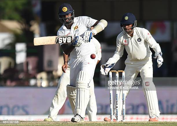 Sri Lankan cricket captain Angelo Mathews plays a shot as Indian wicketkeeper Wriddhiman Saha looks on during the second day of the second Test...