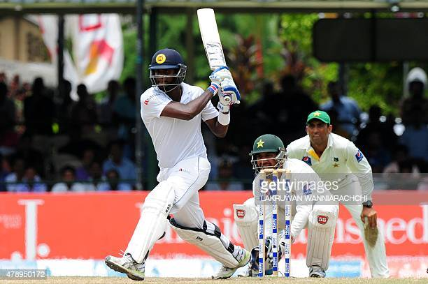 Sri Lankan cricket captain Angelo Mathews plays a shot as Pakistan wicketkeeper Sarfraz Ahmed and fielder Younis Khan look on during the final day of...