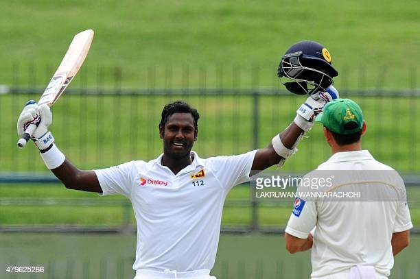 Sri Lankan cricket captain Angelo Mathews raises his bat and helmet in celebration after scoring a century during the fourth day of the third and...