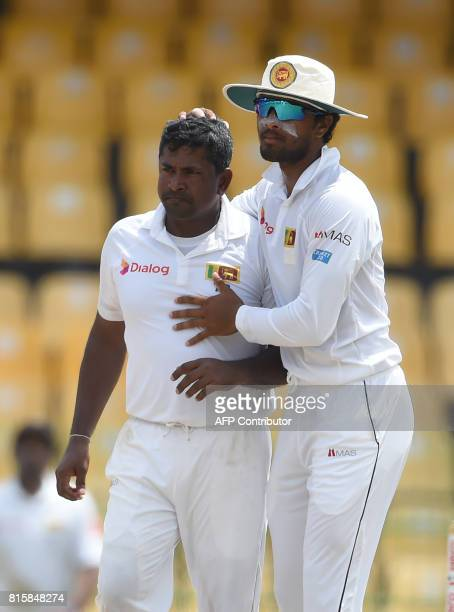 Sri Lankan cricket captain Dinesh Chandimal and Rangana Herath celebrates after he dismissed Zimbabwe cricketer Sikandar Raza during the fourth day...