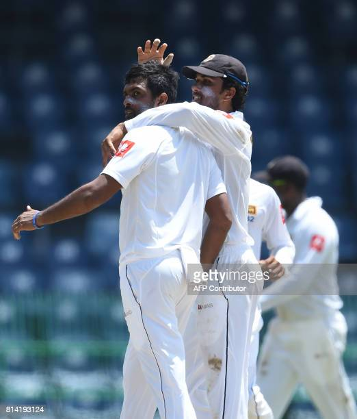 Sri Lankan cricket captain Dinesh Chandimal celebrates with Dilruwan Perera after the dismissal of Zimbabwe cricketer Sean Williams during the first...