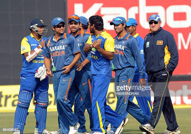Sri Lankan cricket captain Kumar Sangakkara gestures as he speaks with Indian cricketer Suresh Raina as they walk with teammates off the pitch during...