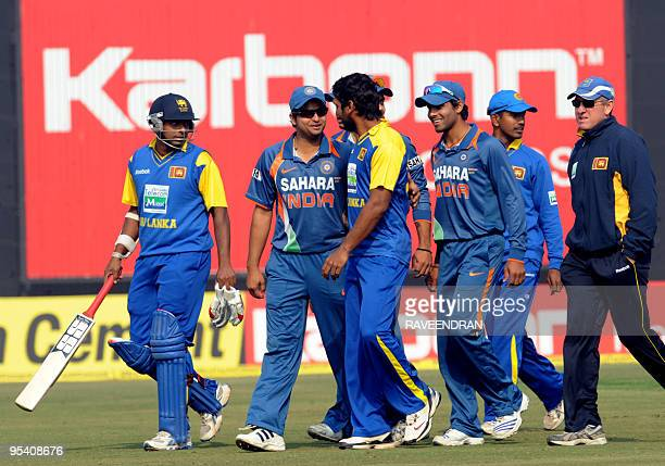Sri Lankan cricket captain Kumar Sangakkara walks with teammates and Indian opponents back to the pavilion after the cancellation of the fifth and...