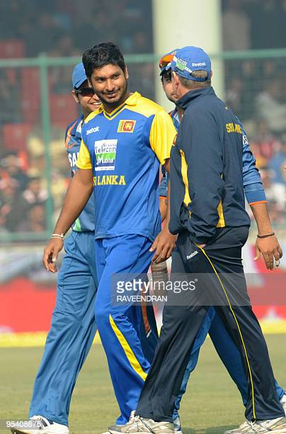 Sri Lankan cricket captain Kumar Sangakkara walks with teammates to the pavilion after the cancellation of the fifth and final One Day International...