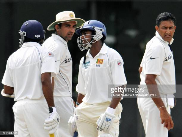 Sri Lankan cricket captain Mahela Jayawardene and teammate Malinda Warnapura talk together as Indian cricket captain Anil Kumble and teammate Zaheer...