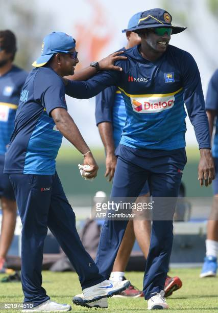 Sri Lankan cricket captain Rangana Herath and Angelo Mathews warm up during a practice session at Galle International Cricket Stadium in Galle on...