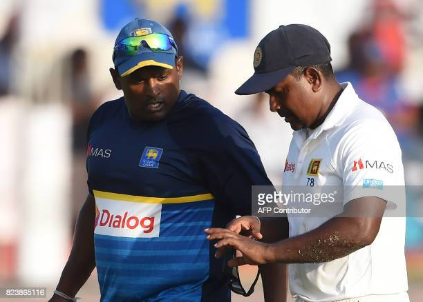 Sri Lankan cricket captain Rangana Herath grimaces in pain after being injured during the third day of the first Test match between Sri Lanka and...
