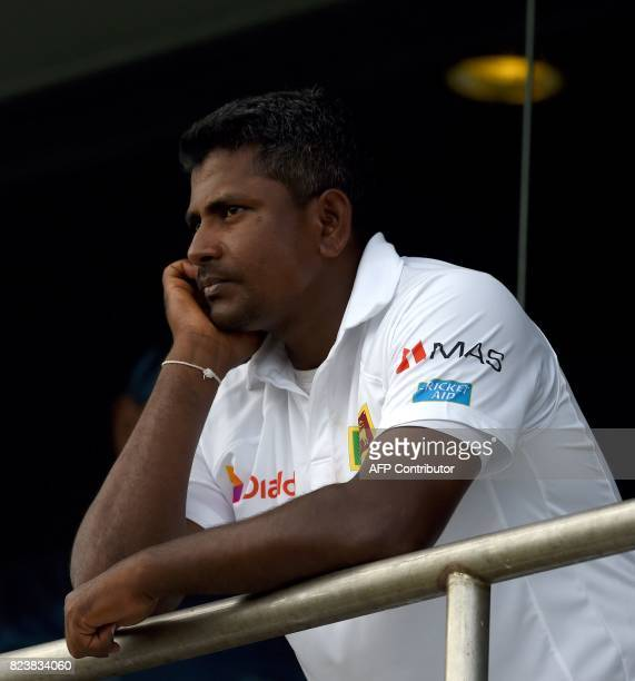 Sri Lankan cricket captain Rangana Herath looks on from the team's dressing room as rain delays play during the third day of the first Test match...